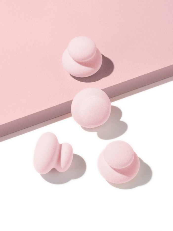 Four small applicator puffs on white and pink surface
